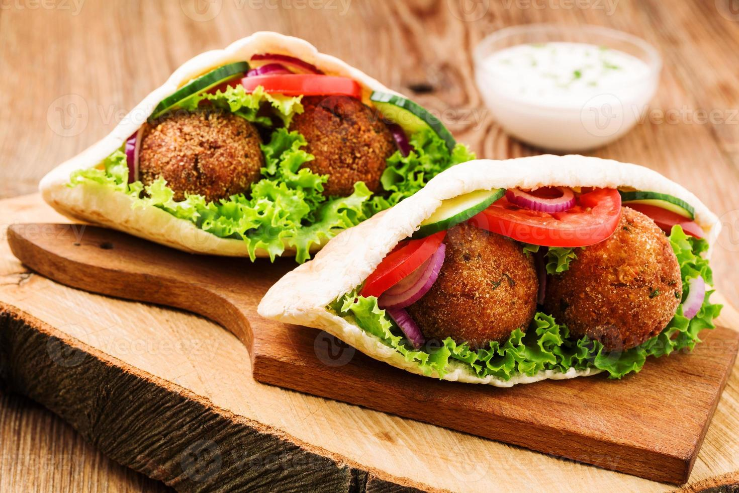 falafel e verdure fresche nel pane pita sul tavolo di legno foto