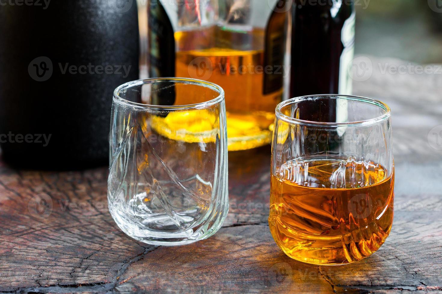 whisky marrone dorato sulle rocce in un bicchiere foto