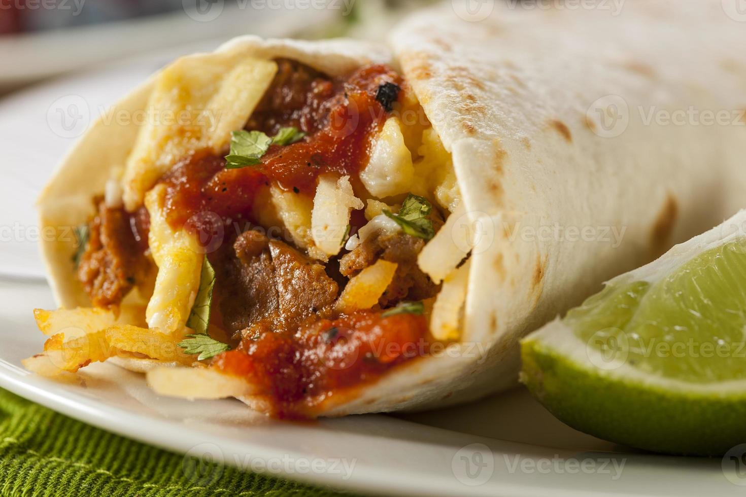 primo piano di abbondante burrito chorizo colazione con lime foto