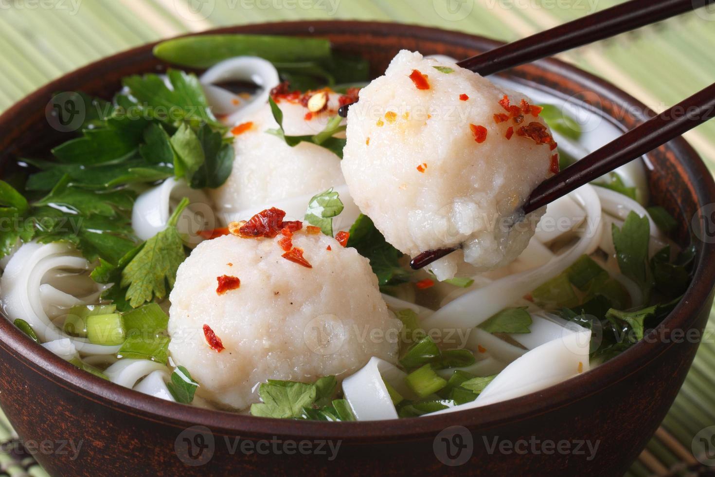 zuppa asiatica tradizionale con polpette di pesce e bacchette foto
