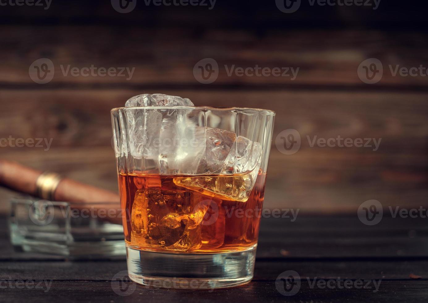 bicchiere di whisky con ghiaccio e sigaro foto