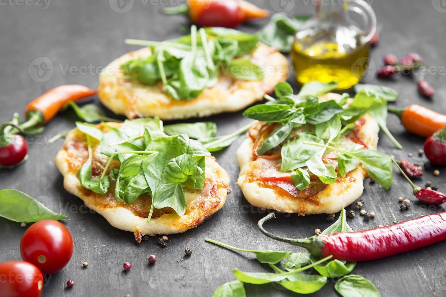 mini pizze con mozzarella, spinaci e basilico fresco foto