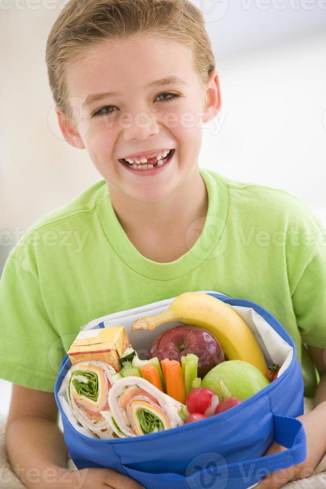 giovane ragazzo che tiene pranzo al sacco foto