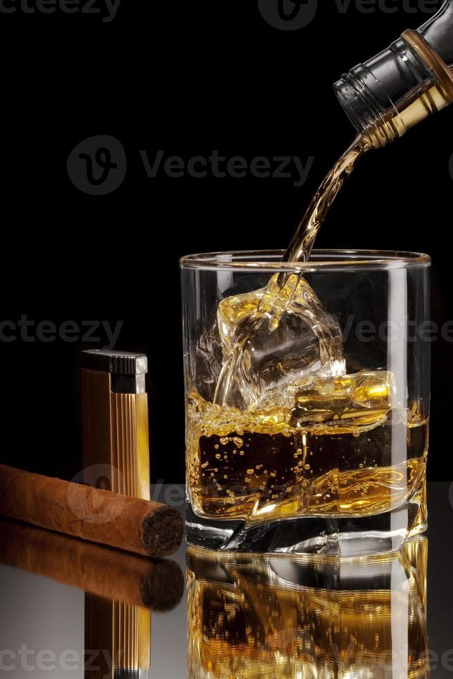 versando rum in un bicchiere con ghiaccio. sigaro e accendino accanto. foto