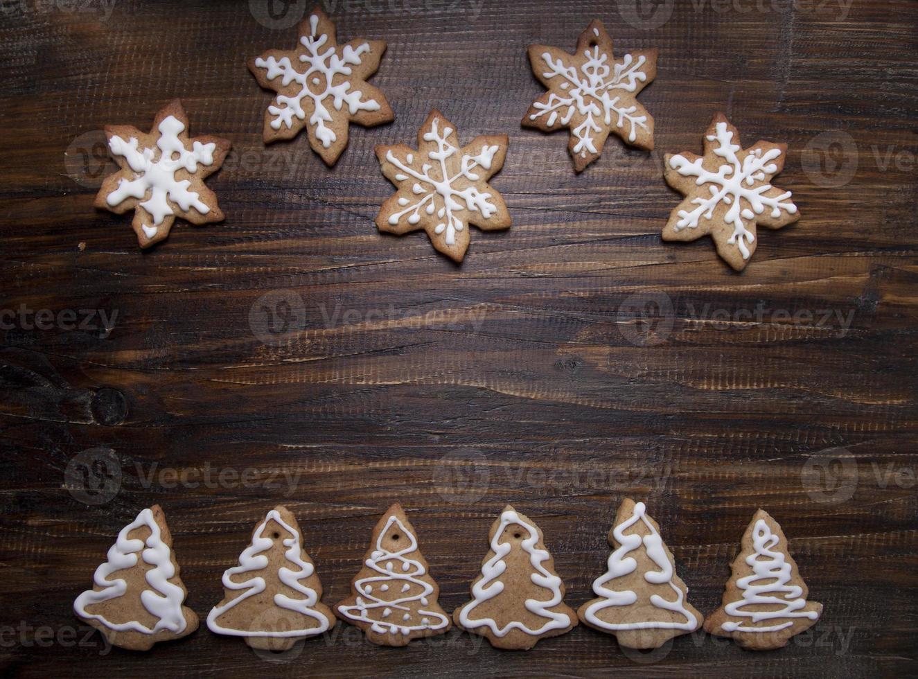 Sfondo di Natale con biscotti decorati con glassa, su una tavola di legno. foto