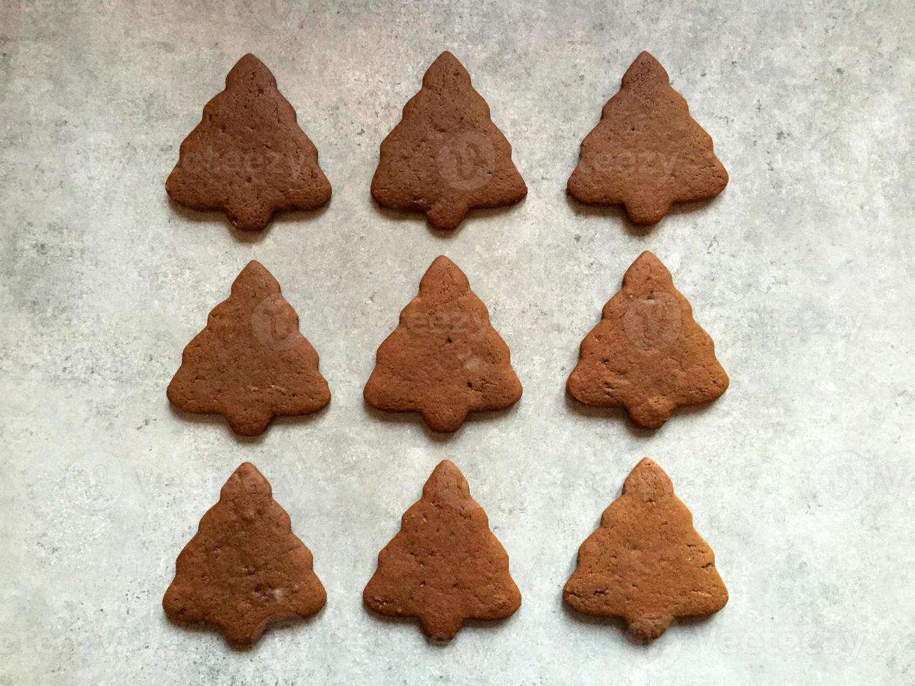 biscotti di panpepato di Natale a forma di alberi sul ripiano della cucina foto