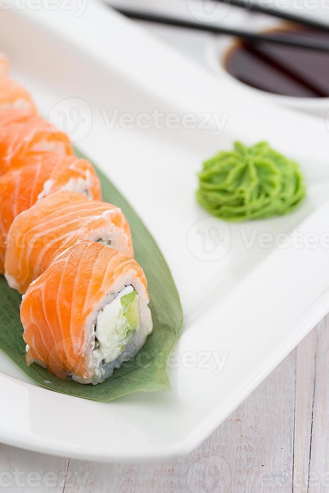 rotolo di sushi di salmone su un piatto bianco con wasabi foto