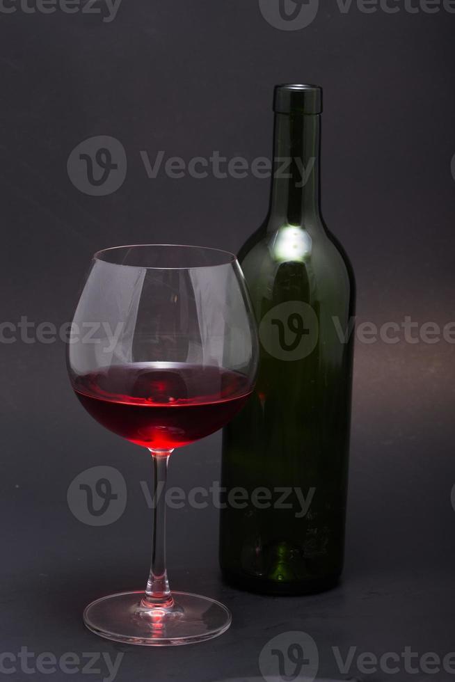 bicchieri da vino, bottiglia e tappi di sughero. isolato su sfondo nero foto
