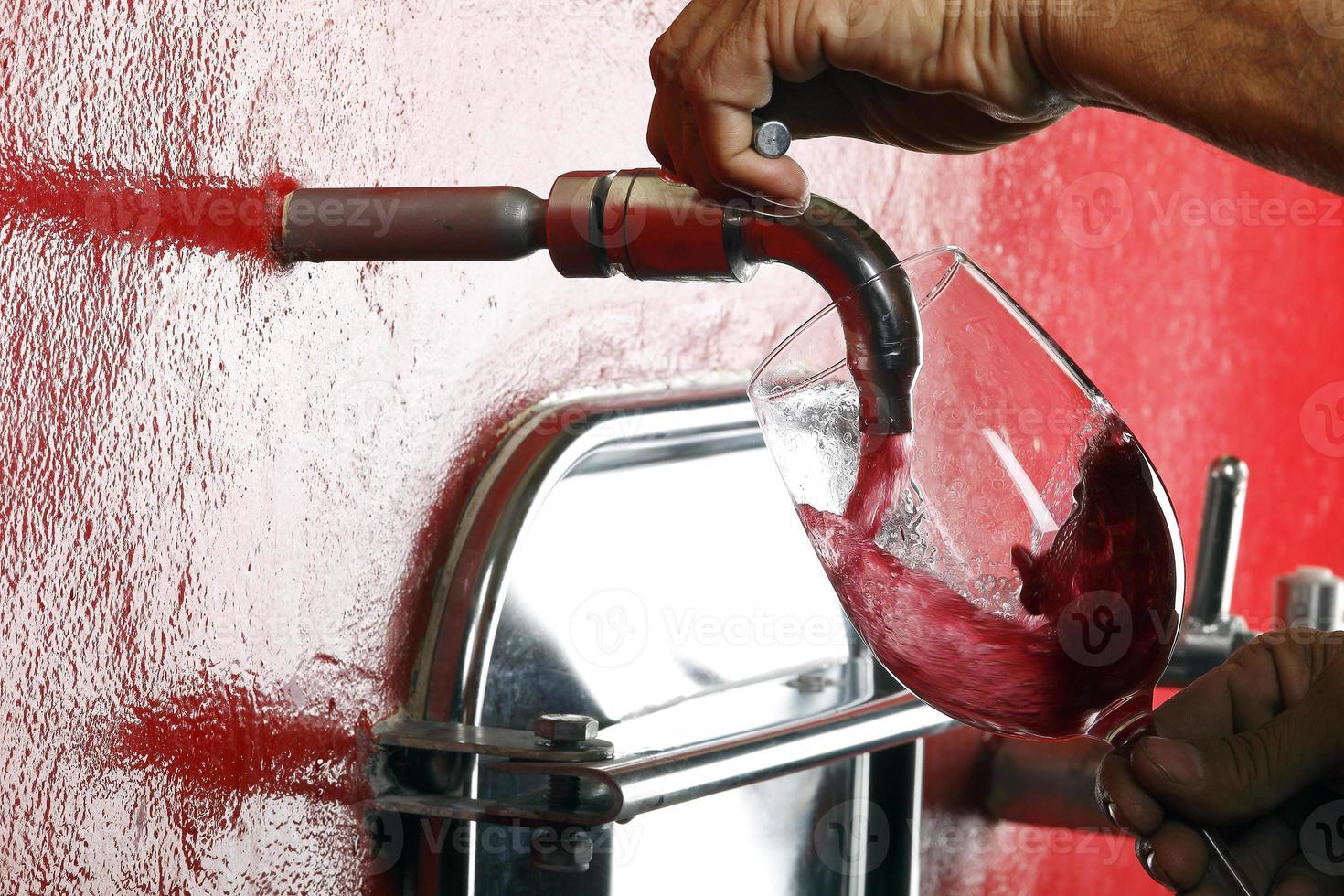 bicchiere di vino rosso rubinetto vigna foto