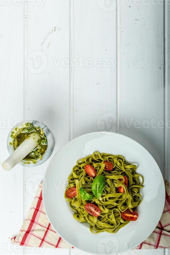 tagliatelle agli spinaci con pesto di basilico e mini pomodori foto