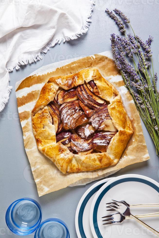 sana torta di mele aperta con lavanda. cucina francese su grigio foto