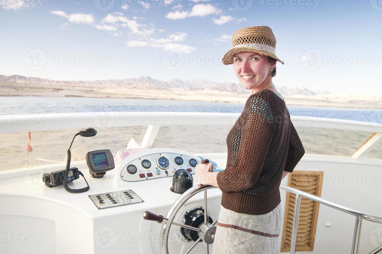 giovane donna attraente che dirige una barca foto