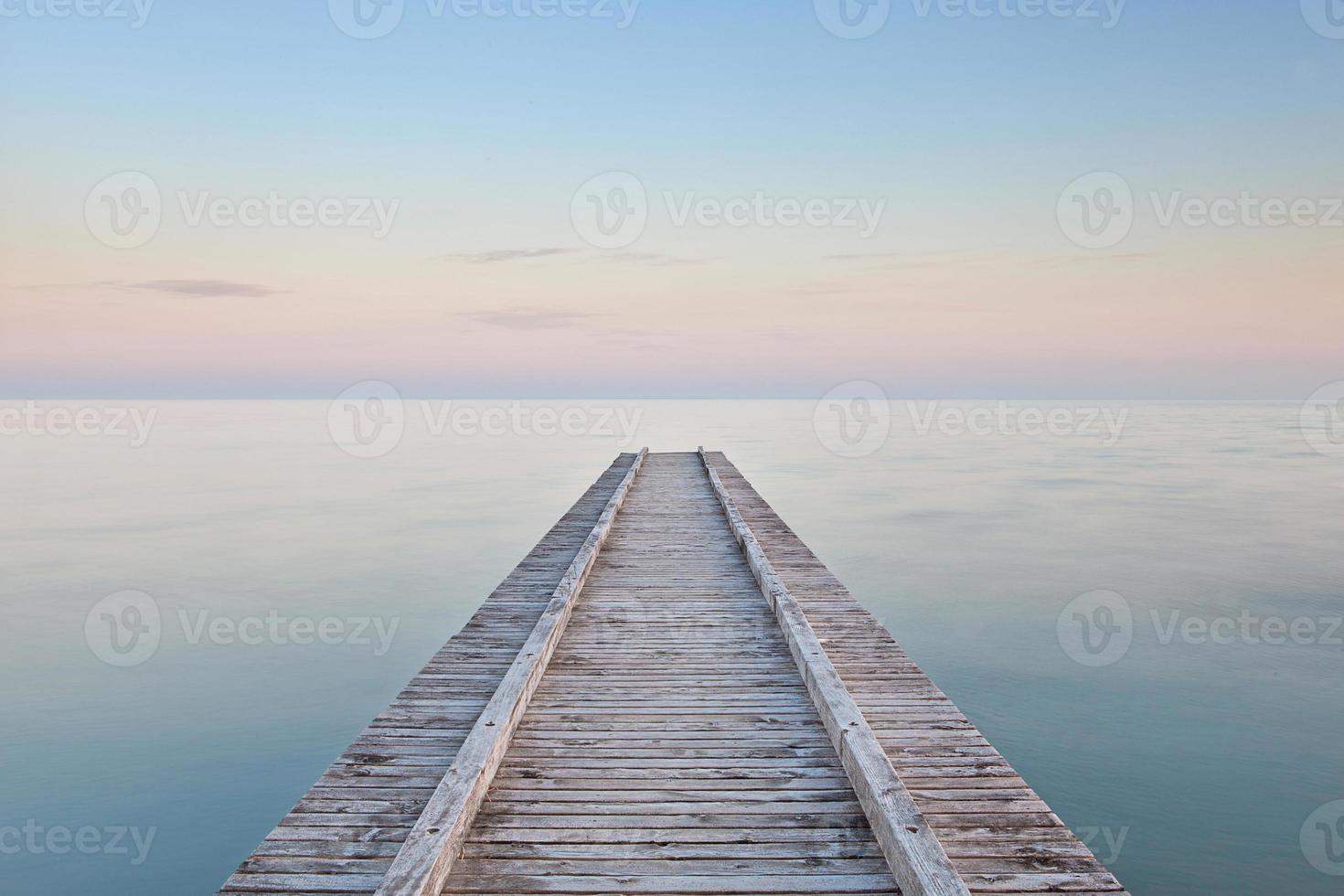molo vuoto che porta verso il mare al tramonto foto