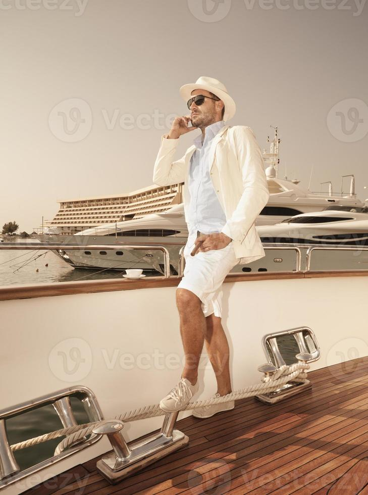 uomo sul ponte di una barca con uno yacht dietro di esso foto
