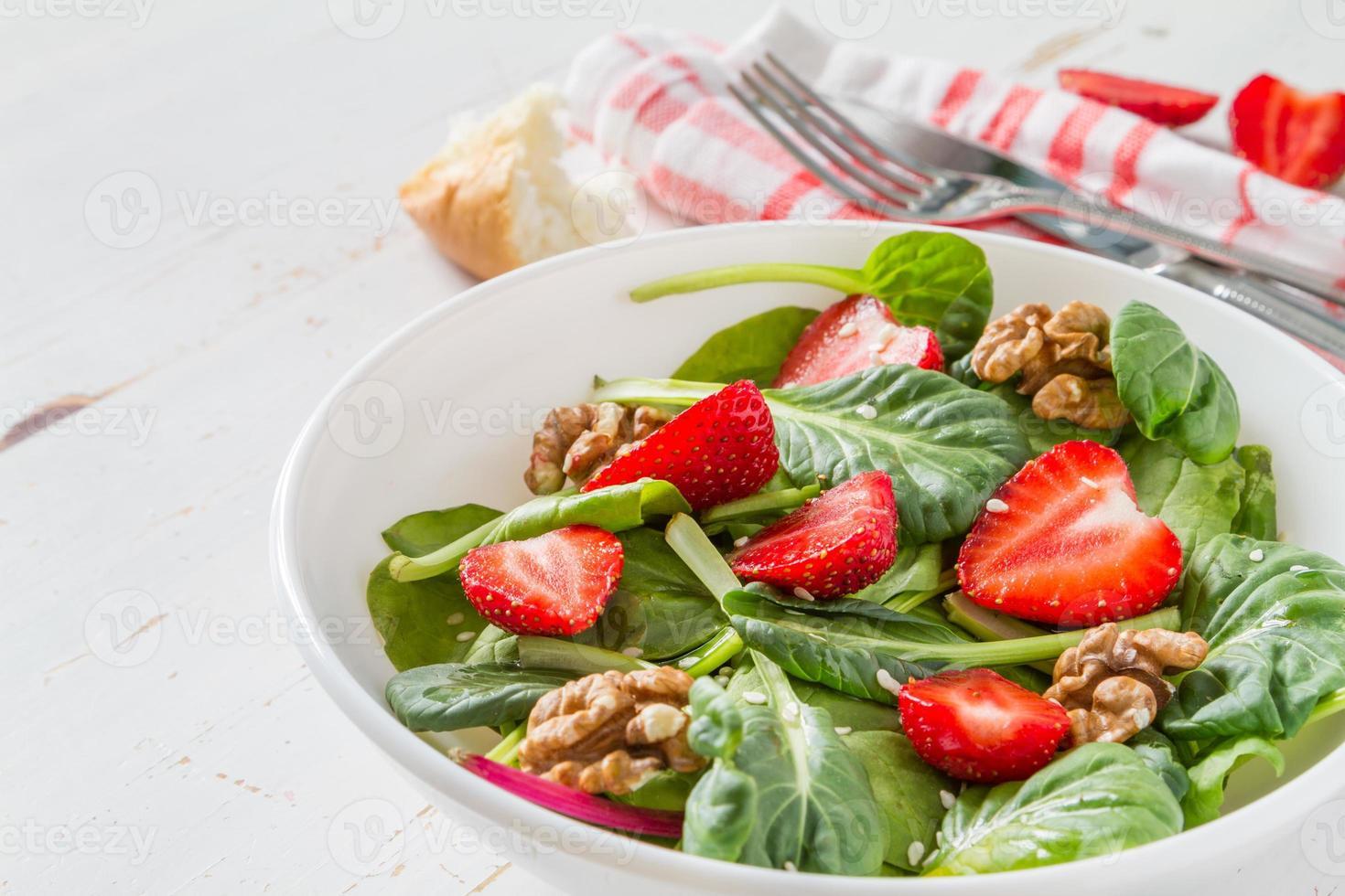insalata con spinaci, fragole, noci, olio, pane, tovagliolo a quadri foto