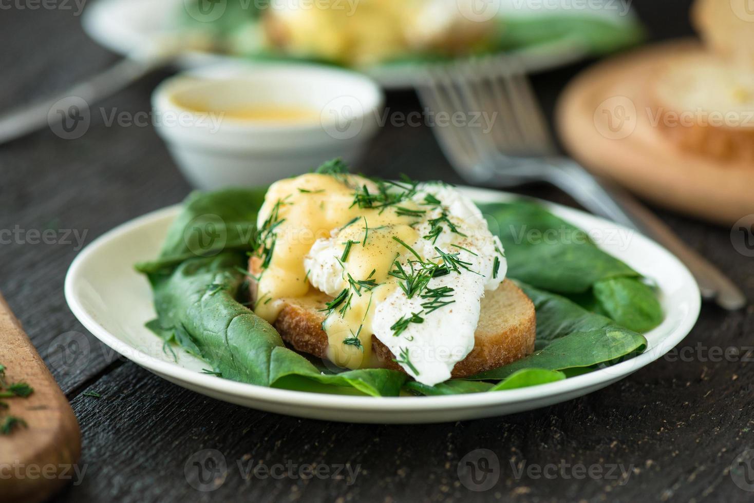 uovo in camicia su un pezzo di pane con spinaci foto