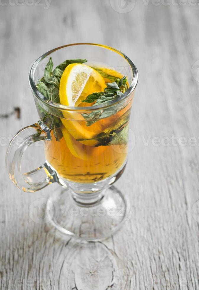tè verde con menta e limone in una tazza di vetro foto