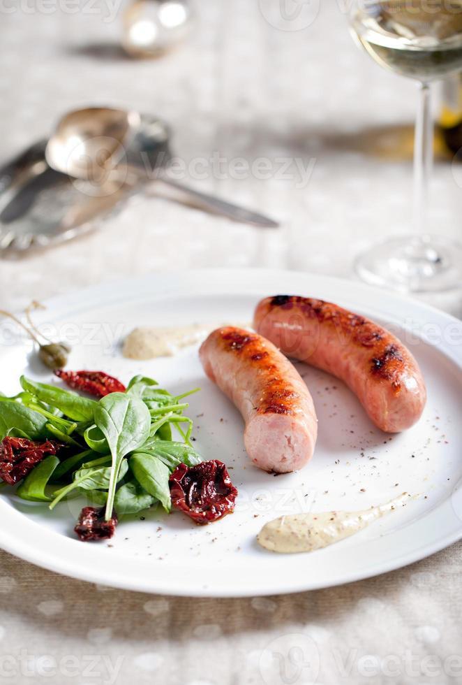 salsicce alla griglia con insalata su un piatto bianco foto