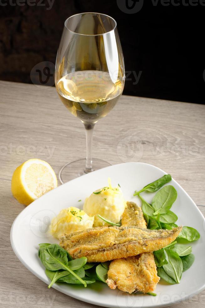 cena, filetto di pesce con patate, spinaci giovani foto
