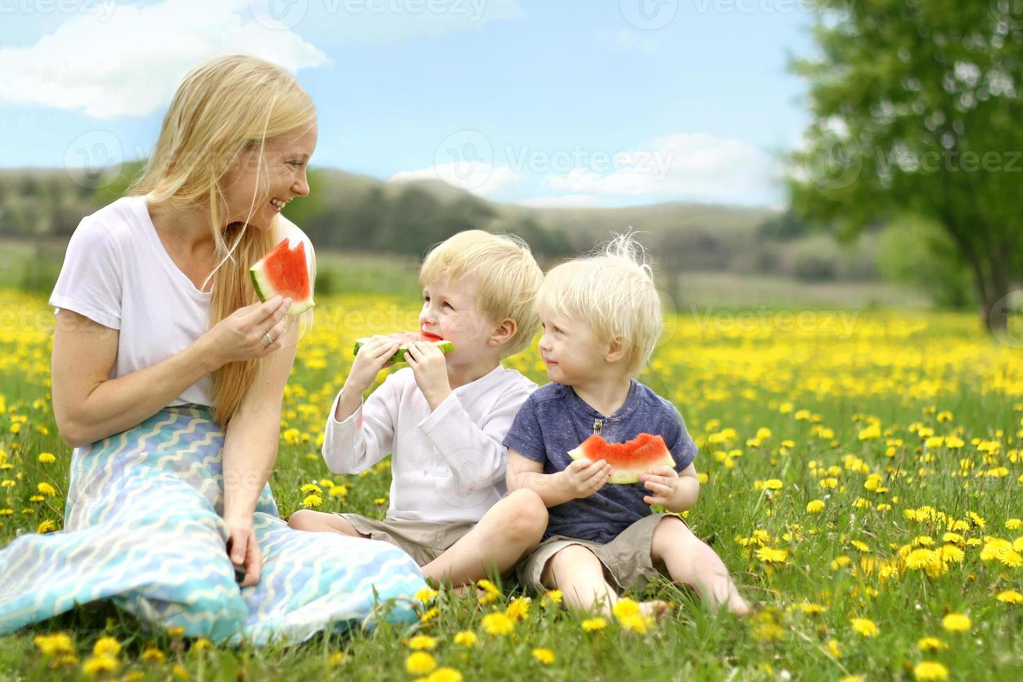 madre e bambini che mangiano frutta nel prato di fiori foto