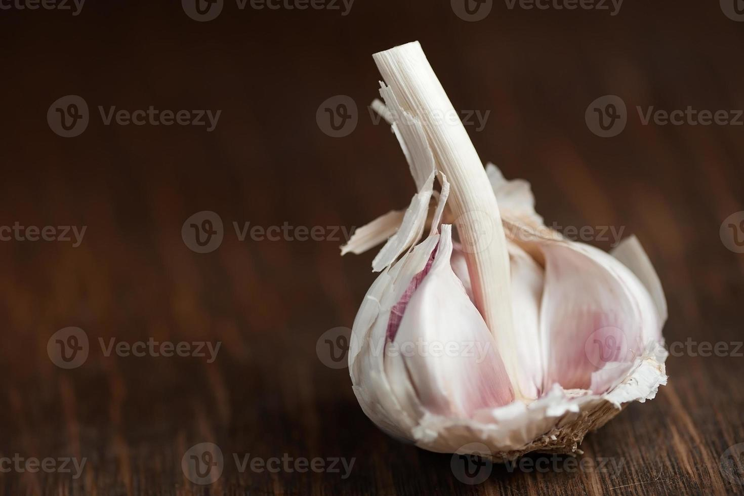 lampadina dell'aglio che riposa sul tagliere di legno foto