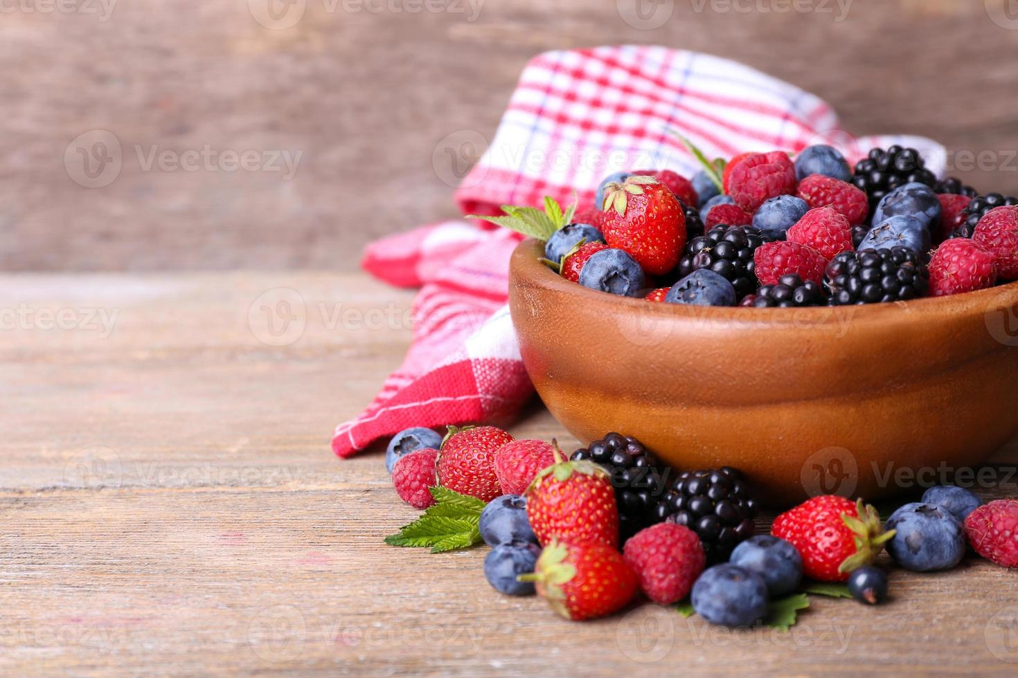 bacche mature dolci differenti in ciotola, sulla vecchia tavola di legno foto