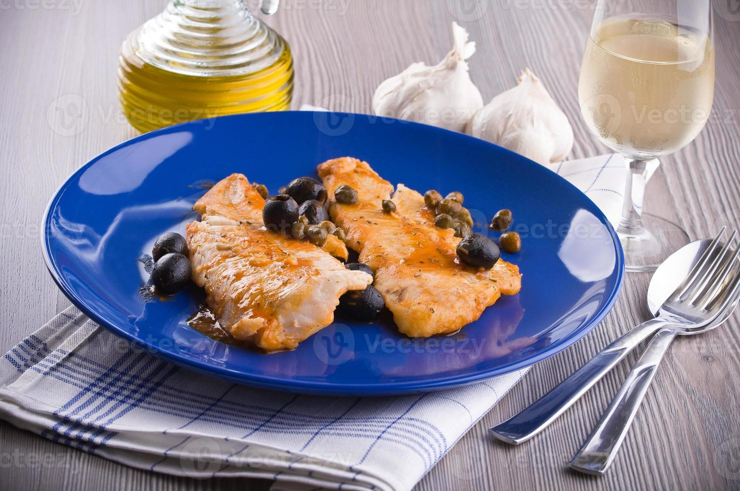 filetto di pesce con olive nere e capperi. foto