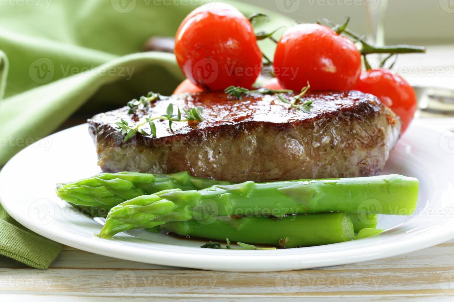 bistecca di manzo alla griglia con contorno di verdure (asparagi e pomodori) foto