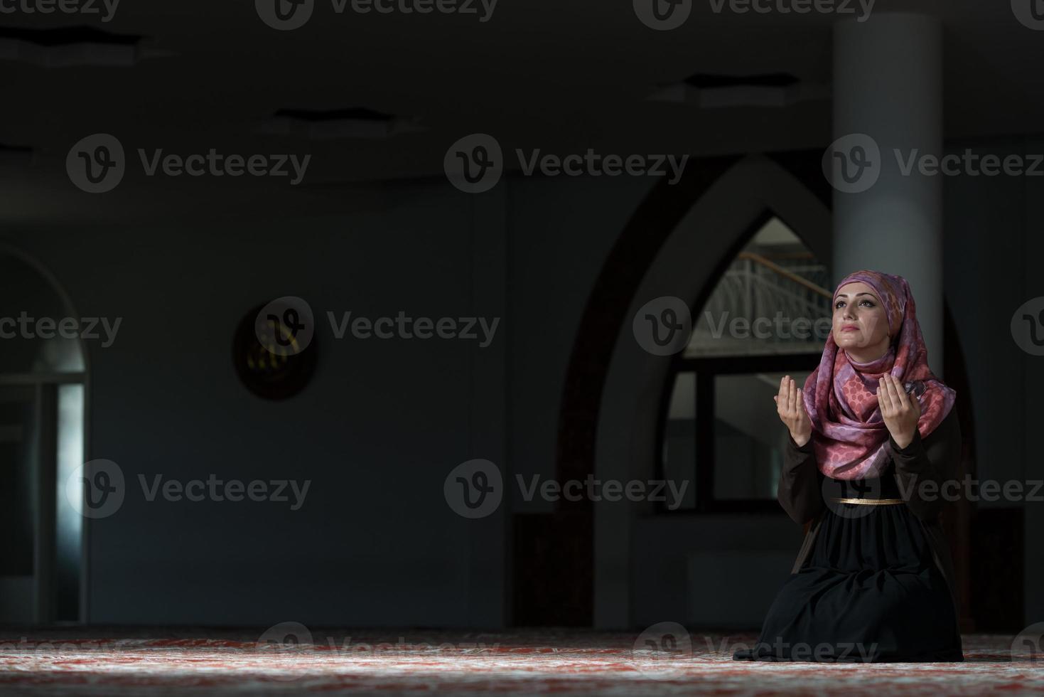 giovane donna musulmana che prega nella moschea foto