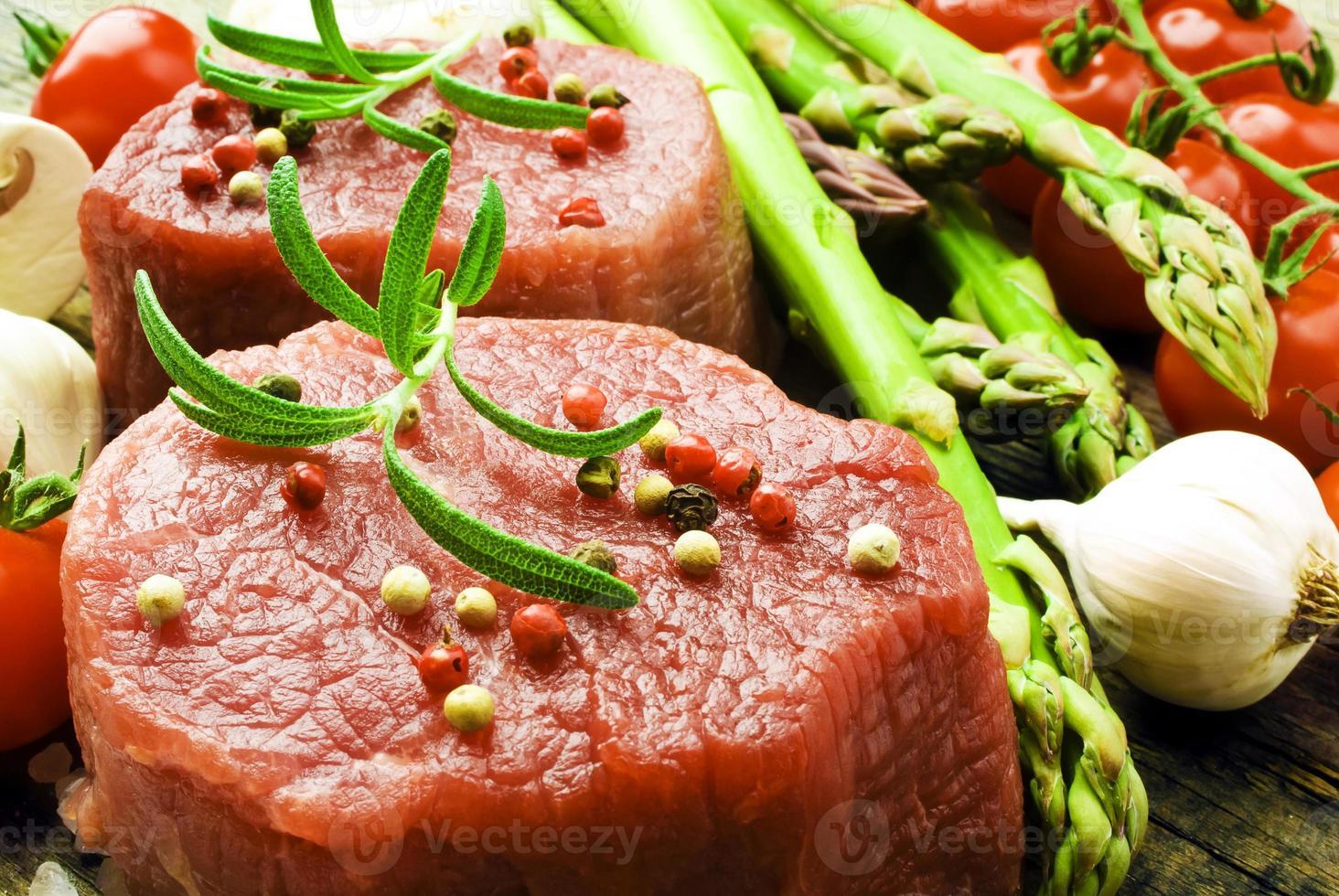 bistecca cruda con asparagi verdi su tavola di legno foto