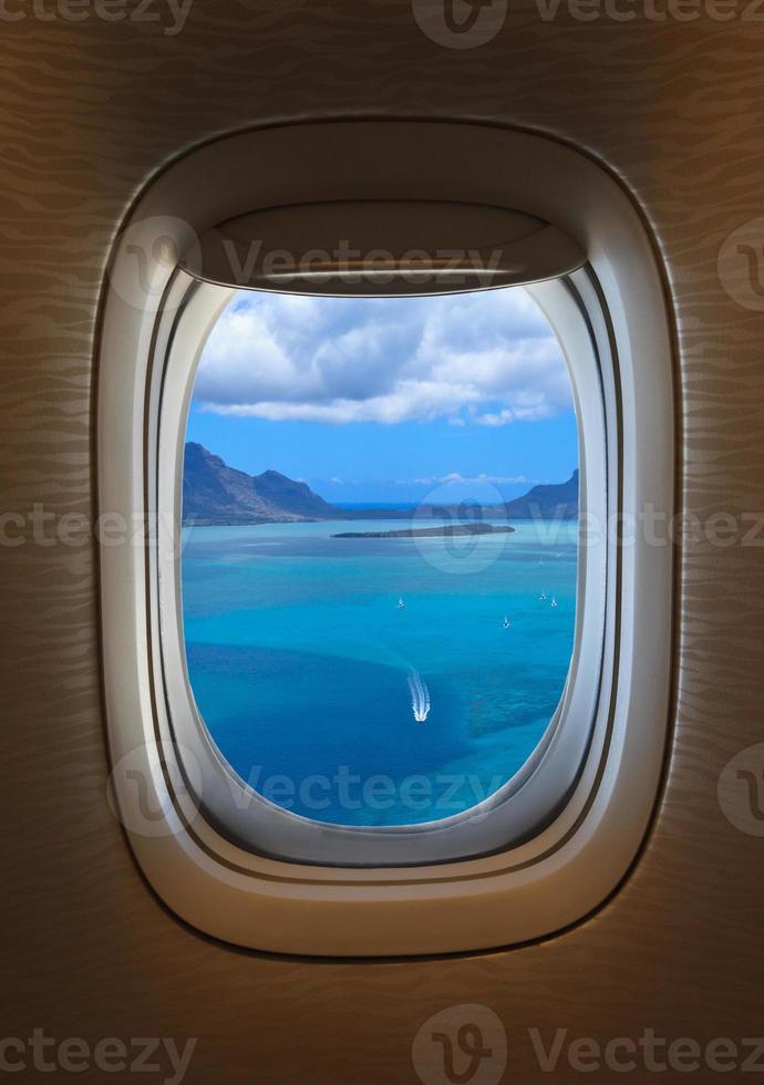 finestra dell'aeroplano con una vista di un mare blu all'esterno foto