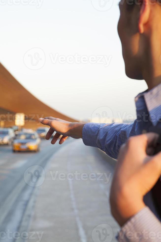giovane viaggiatore che ferma un taxi fuori dall'aeroporto foto