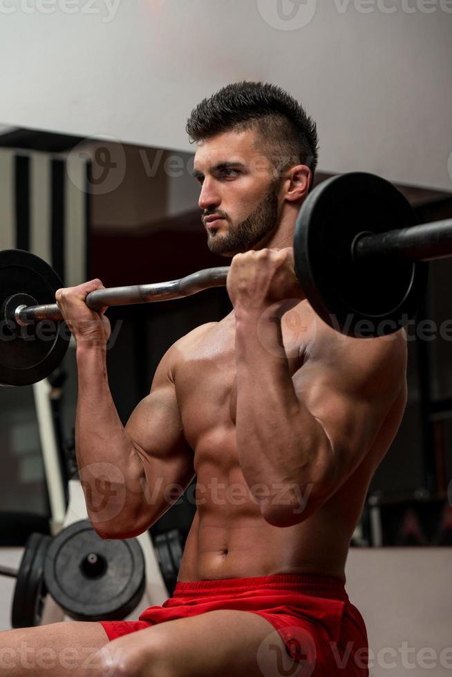 uomo muscolare che esercita il bicipite foto
