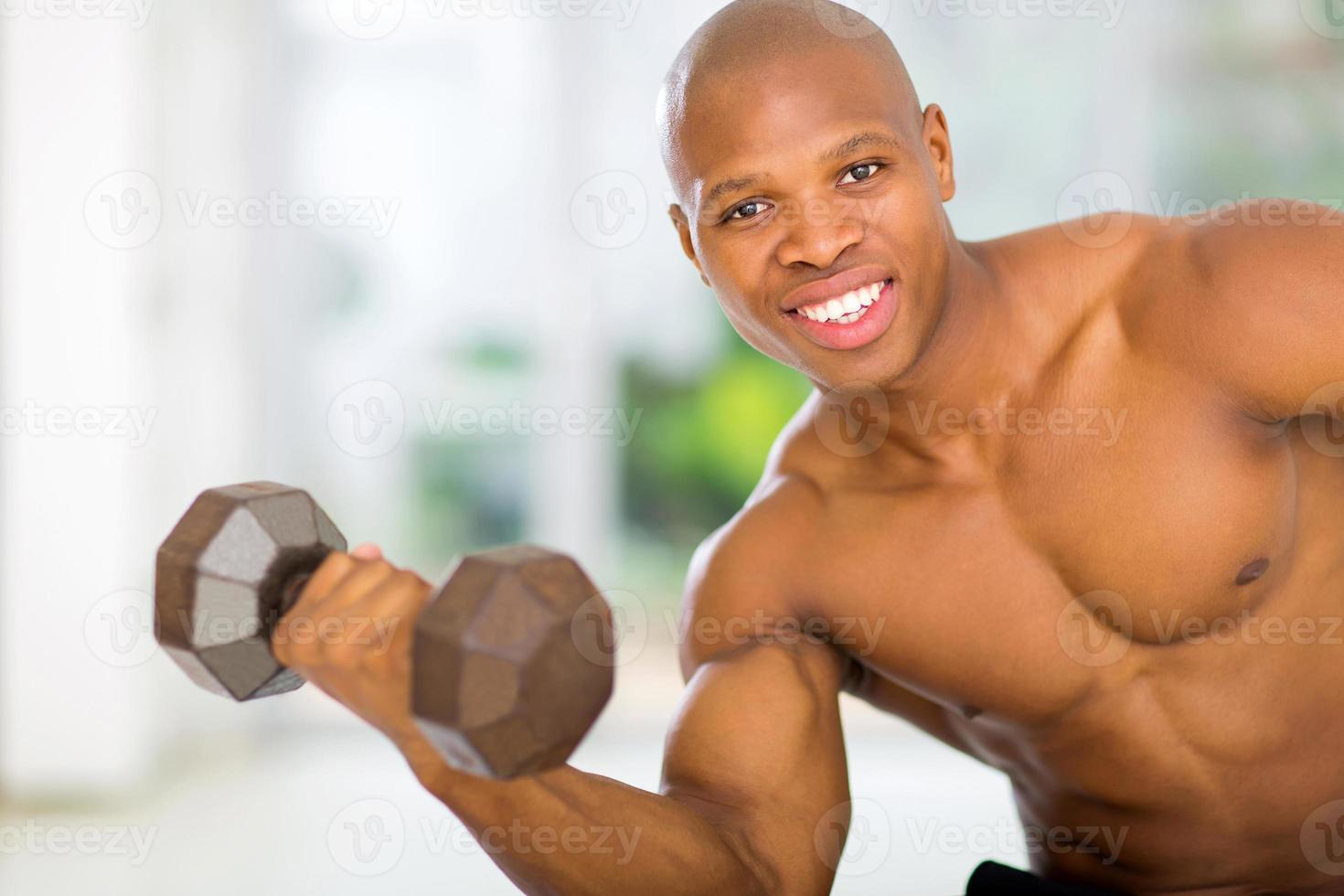 uomo africano che si esercita con le teste di legno a casa foto