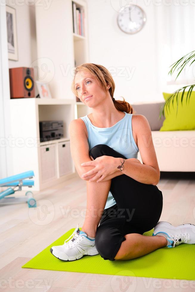 la giovane donna attraente e in buona salute che fa la forma fisica esercita la casa di allenamento foto