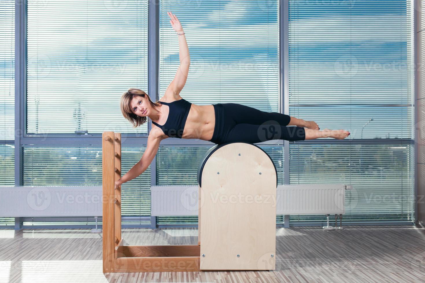 concetto dei pilates, di forma fisica, di sport, di addestramento e della gente - donna sorridente foto