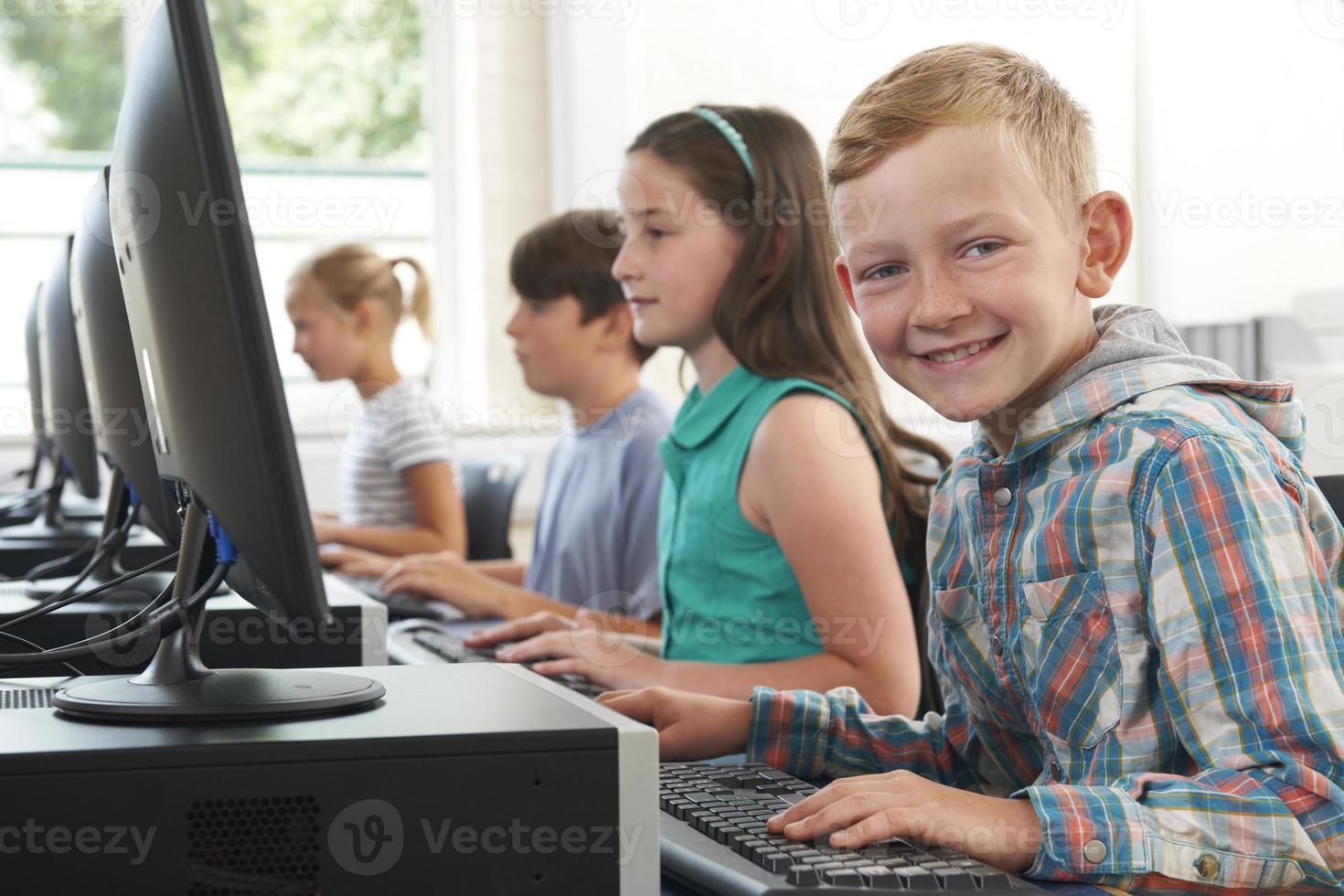 gruppo di bambini delle scuole elementari in classe di computer foto