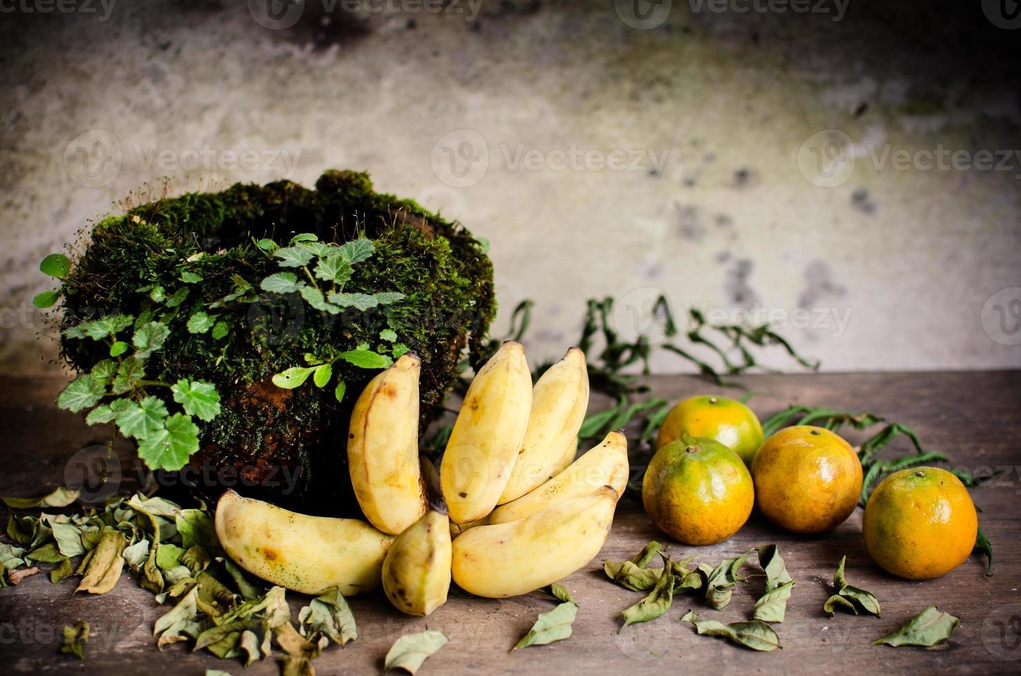 arance a banana e coperchio in vaso di ceramica con muschio foto