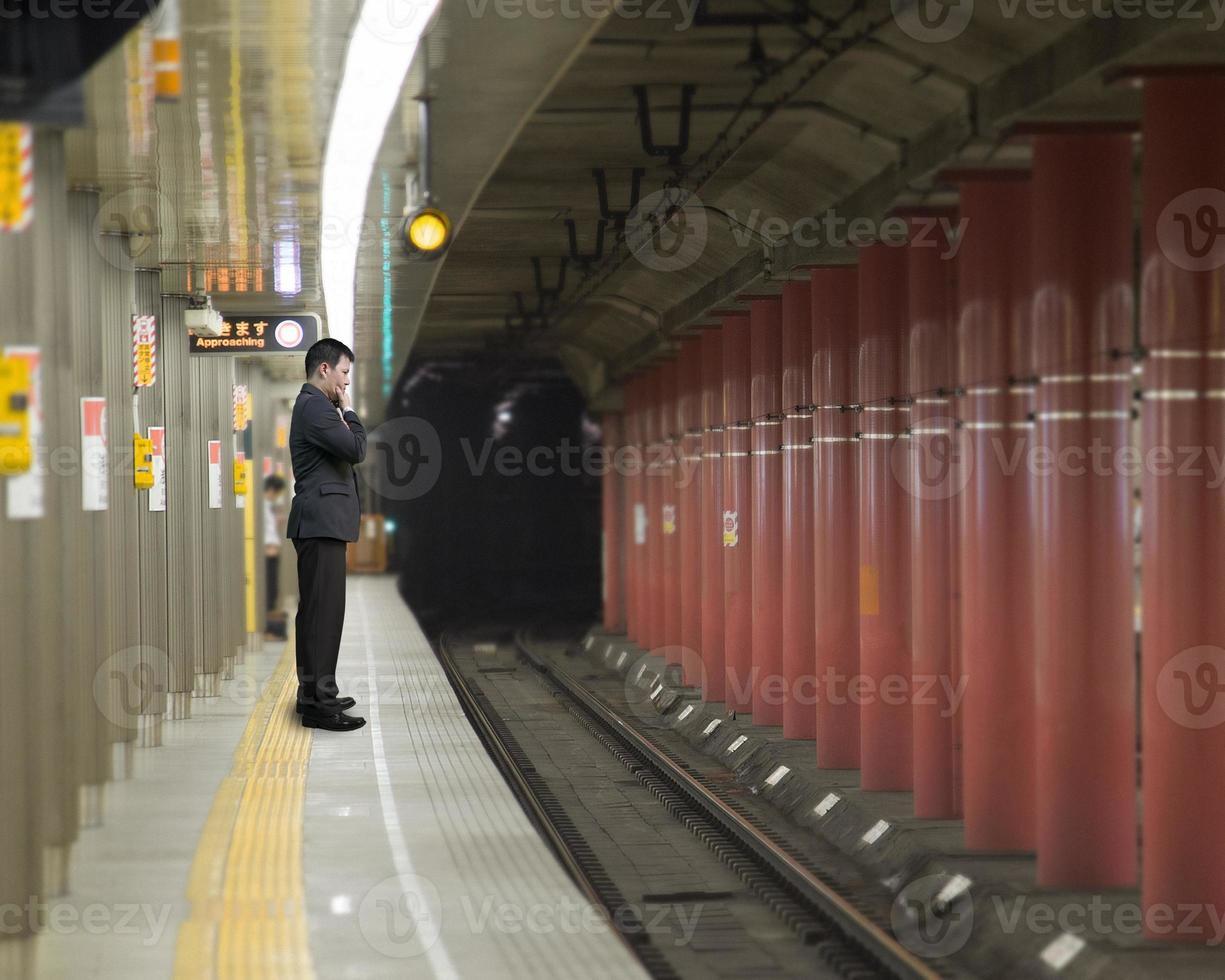 uomo d'affari pensando e in piedi sulla piattaforma foto
