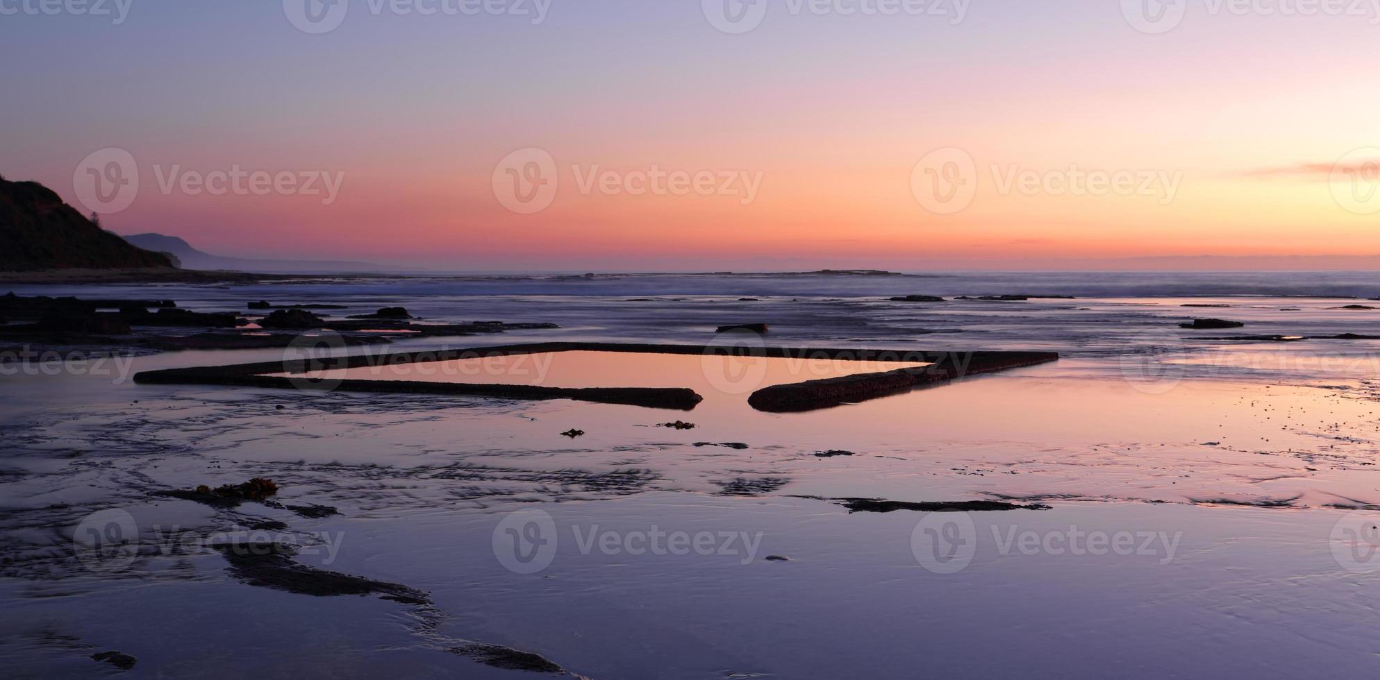 la piscina per bambini sullo scaffale roccioso all'alba foto