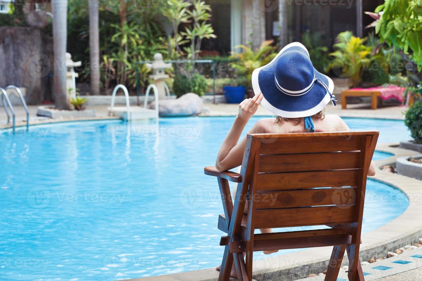 donna che si distende vicino alla piscina foto