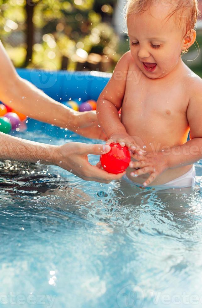 giocare e spruzzi d'acqua in una piscina foto