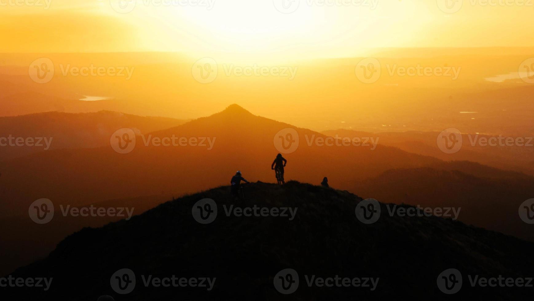 sagoma di mountain bike in cima alla collina al tramonto foto