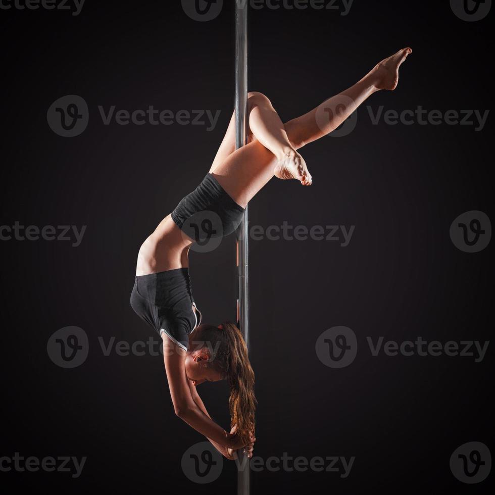 ballo del palo di esercizio della donna su fondo grigio foto