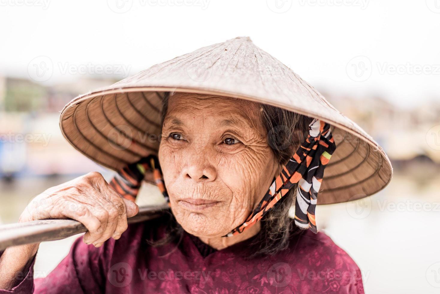vecchia donna amichevole con cappello di paglia vietnamita foto