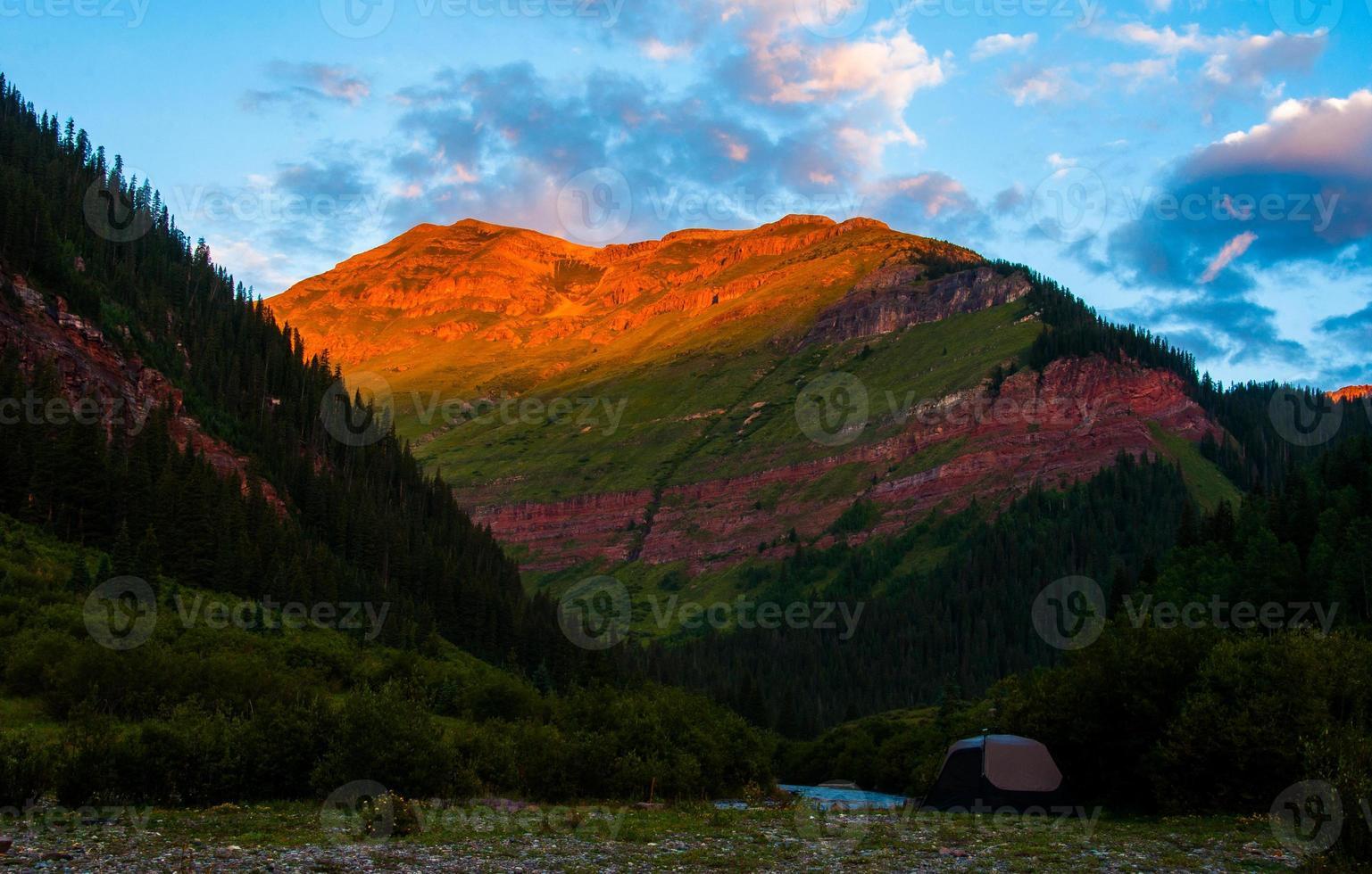 Alba di montagna rocciosa con bagliore alpino campeggio con tenda foto