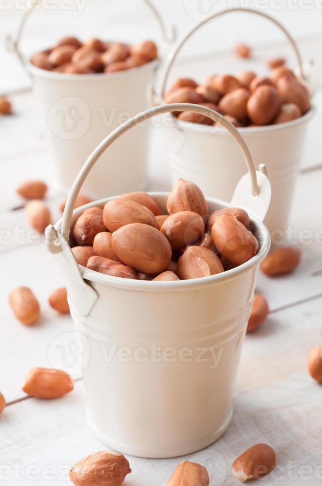arachidi o arachidi crude in secchio bianco foto