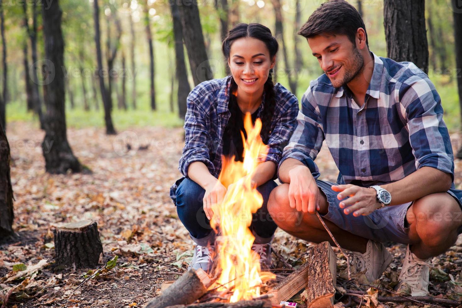 coppia e falò nella foresta foto