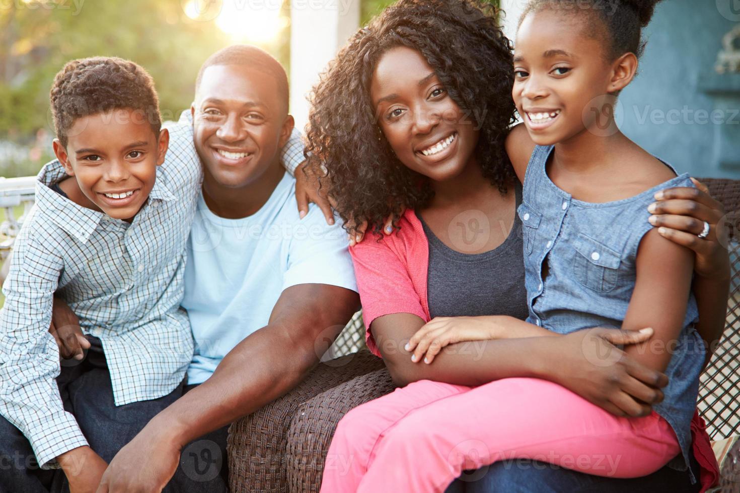Ritratto di famiglia seduto fuori casa foto