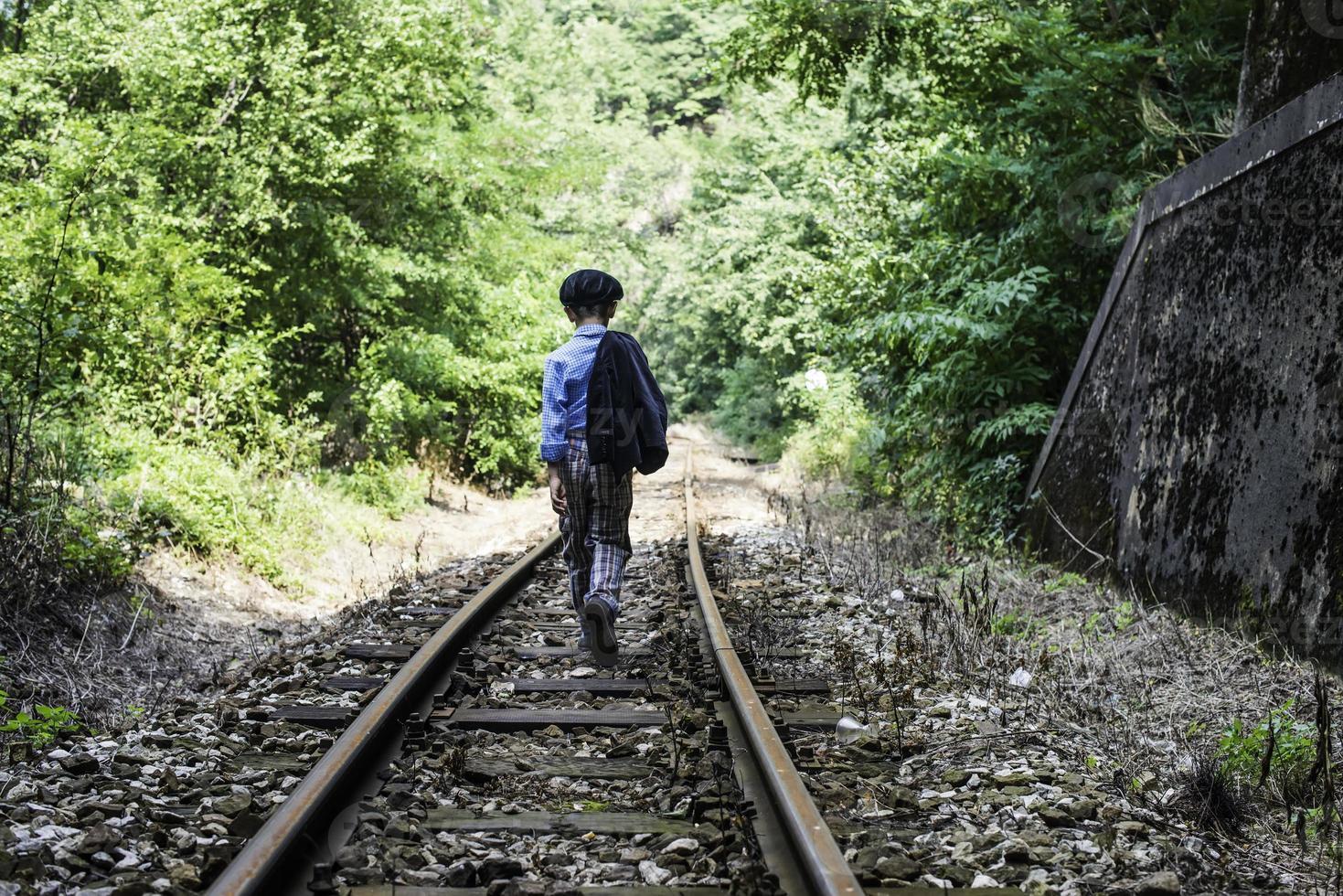 bambino che cammina sulla ferrovia foto